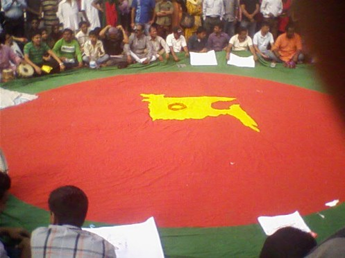 People gather around a huge old flag, where the map of Bangladesh embossed/stitched on  the red circle