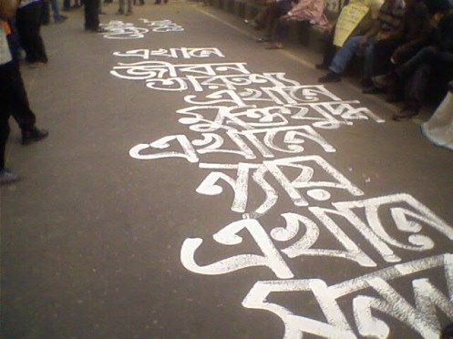 A road graffiti reading  'Life is here,  Fountain of youth is here, Struggle for freedom is here, Conscience is here, So is the beauty'