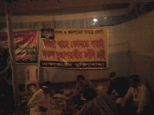 A banner reads popular dialogue of a stage drama called Nural Dine er Sara Jibon , 'Wake Up. Where is everyone?'